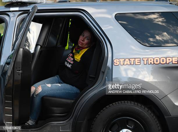 An arrested activist looks out from a state trooper vehicle after activists and members of different tribes from the region blocked the road to Mount...