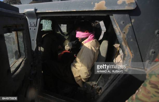 TOPSHOT An arrested man sits in an army vehicle in Mosul's southern neighbourhood of Jawasaq on February 24 2017 during an ongoing offensive by Iraqi...