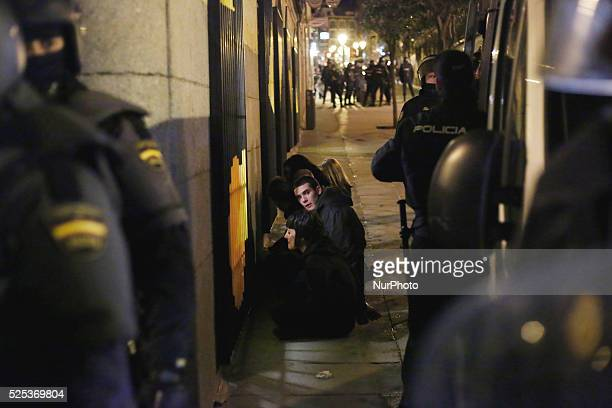 An arrested protestor looks at riot police while they wait to be transferred to the police station during a protest against the 'Clamp law' in Madrid...