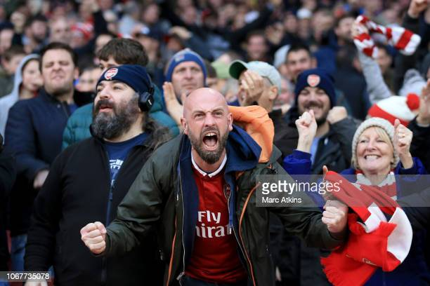 An Arsenal fan celebrates during the Premier League match between Arsenal FC and Tottenham Hotspur at Emirates Stadium on December 2 2018 in London...