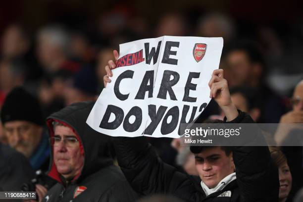 An Arsenal fan holds a sign saying 'We care do you' during the UEFA Europa League group F match between Arsenal FC and Eintracht Frankfurt at...