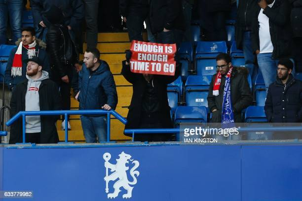 An Arsenal fan holds up a banner calling on Arsenal's French manager Arsene Wenger to quit during the English Premier League football match between...