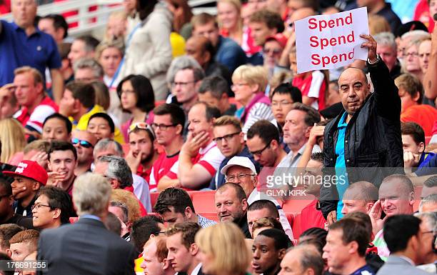 An Arsenal fan holds up a poster bearing the message 'spend spend spend' to Arsenal's French manager Arsene Wenger during the English Premier League...
