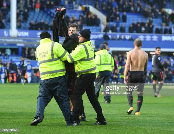 An Arsenal fan holds up Jack Wilshere's shirt as he's escorted off the pitch after the Premier League match between Everton and Arsenal at Goodison...