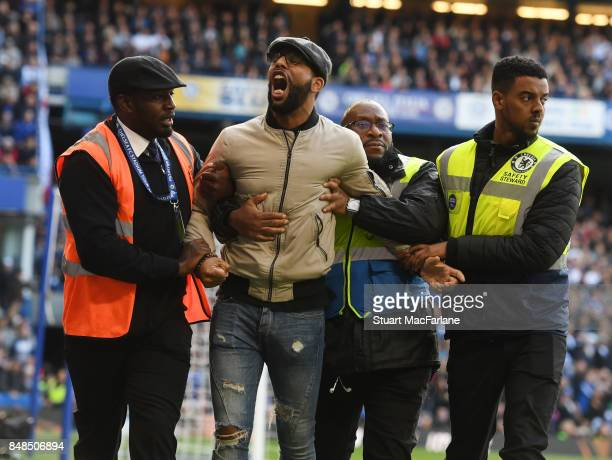 An Arsenal fan is escorted off the pitch by stweards during the Premier League match between Chelsea and Arsenal at Stamford Bridge on September 17...