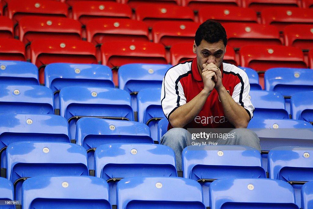 An Arsenal fan looks dejected  : News Photo