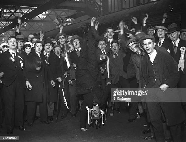 An Arsenal fan performs a one handed handstand at Euston Station to entertain his fellow supporters on their way to Birmingham for the F A Cup replay...
