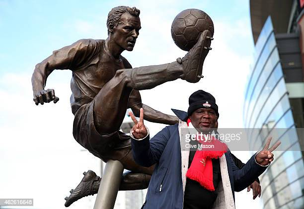 An Arsenal fan poses with the statue of Dennis Bergkamp prior to kickoff during the Barclays Premier League match between Arsenal and Aston Villa at...