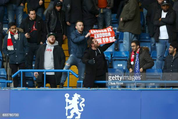 An Arsenal fan shows his discontent as he holds a sign aloft during the Premier League match between Chelsea and Arsenal at Stamford Bridge on...