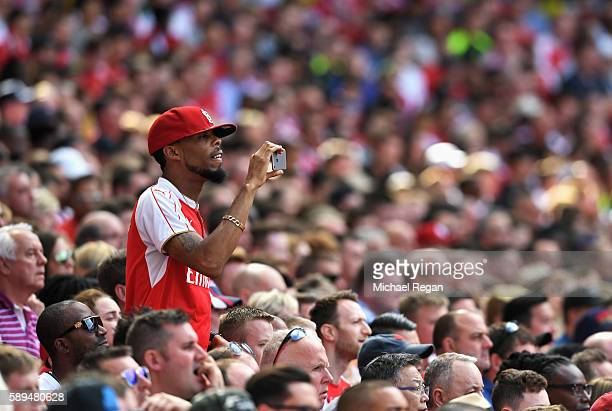 An Arsenal fan takes a photo during the Premier League match between Arsenal and Liverpool at Emirates Stadium on August 14 2016 in London England