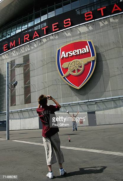 An Arsenal fan takes a picture of anotehr fan outside the new Emirates Stadium during an Arsenal Training and Emirates Stadium Open Day at the...