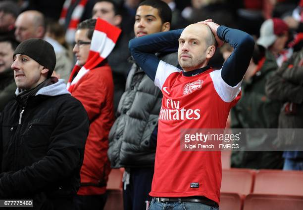 An Arsenal fans looks dejected in the stands after the final whistle
