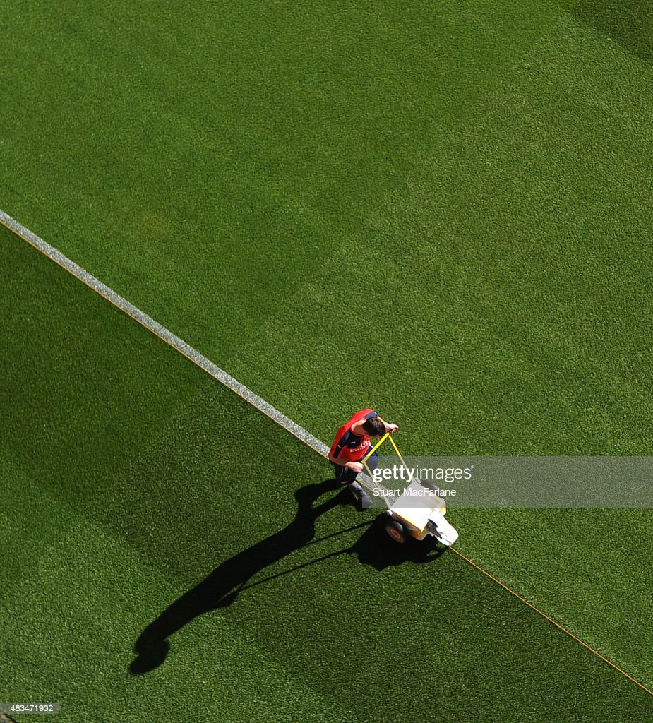 An Arsenal groundsman mark out the pitch before the Barclays Premier League match between Arsenal and West Ham United at Emirates Stadium on August 9, 2015 in London, England.
