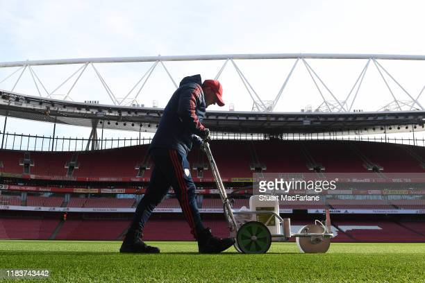 An Arsenal groundsman marks out the pitch before the Premier League match between Arsenal FC and Crystal Palace at Emirates Stadium on October 27,...