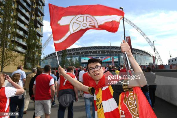 An Arsenal supporter holds up a flag as he arrives at Wembley Stadium in London on May 27 2017 ahead of the English FA Cup final football match...