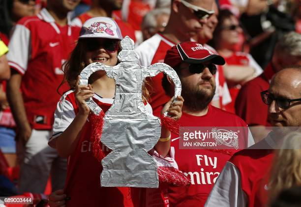 An Arsenal supporter holds up a tin foil FA Cup trophy ahead of the English FA Cup final football match between Arsenal and Chelsea at Wembley...