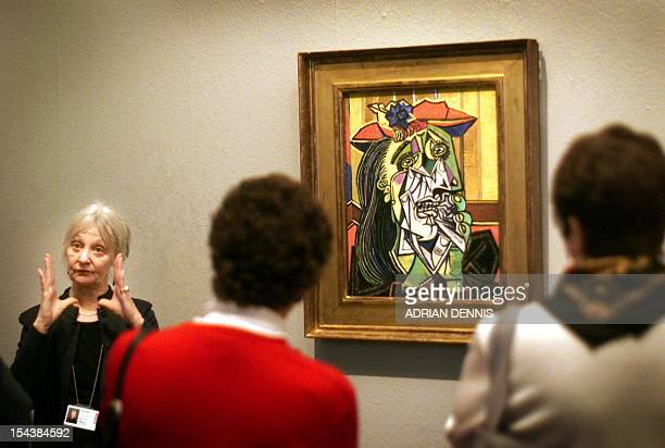 An art gallery tour guide explains 'Weeping Woman' a painting by Pablo Picasso hanging in The Tate Gallery in London 29 February 2000 The painting...