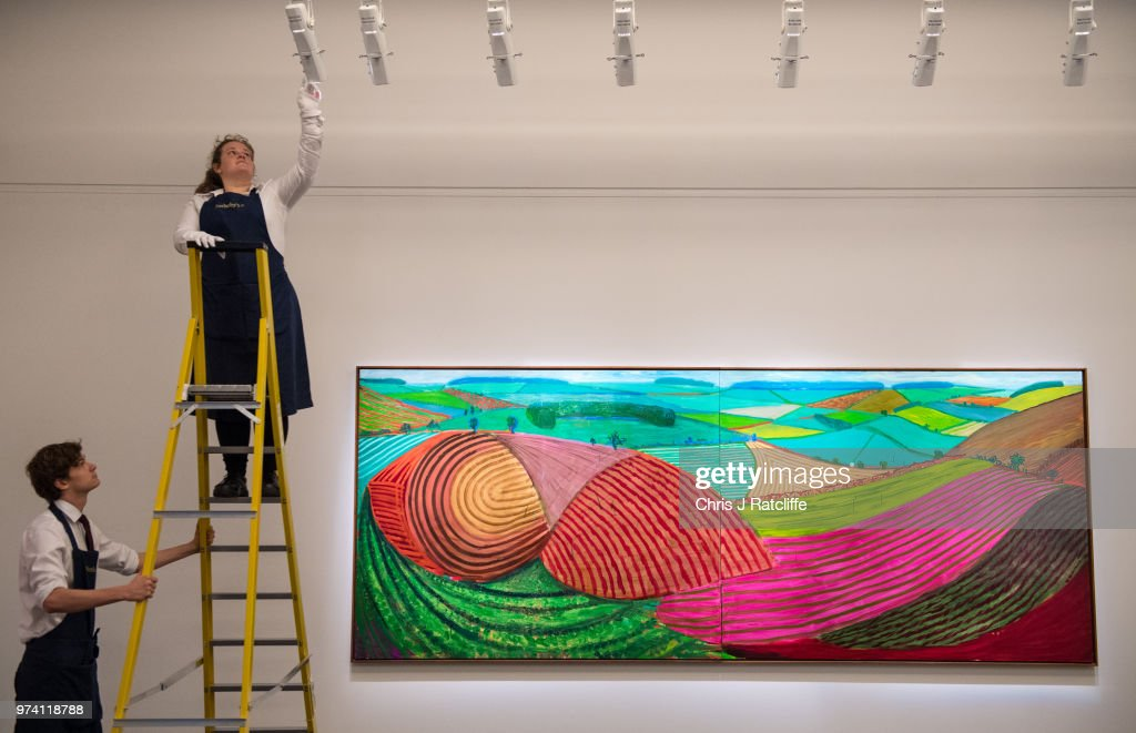 An art handler adjusts lighting above 'Double East Yorkshire' by David Hockney (estimated at £10 million to £15 million) during a preview of the Contemporary Art sale at Sotheby's on June 14, 2018 in London, England. The sale will take place on 26 June 2018 and includes works by artists Hockney, Freud and Basquiat.