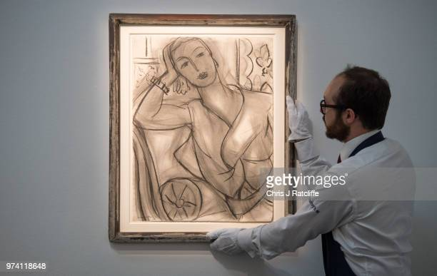 An art handler adjusts 'Portrait of Mrs Hutchinson' by Henri Matisse during a preview of the Impressionist and Modern sale at Sotheby's on June 14...