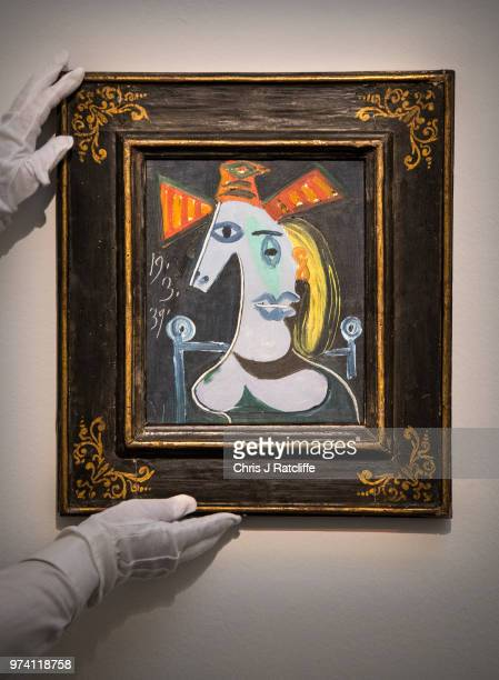 An art handler adjusts 'Tete de femme au chapeau orange' by Pablo Picasso during a preview of the Impressionist and Modern sale at Sotheby's on June...