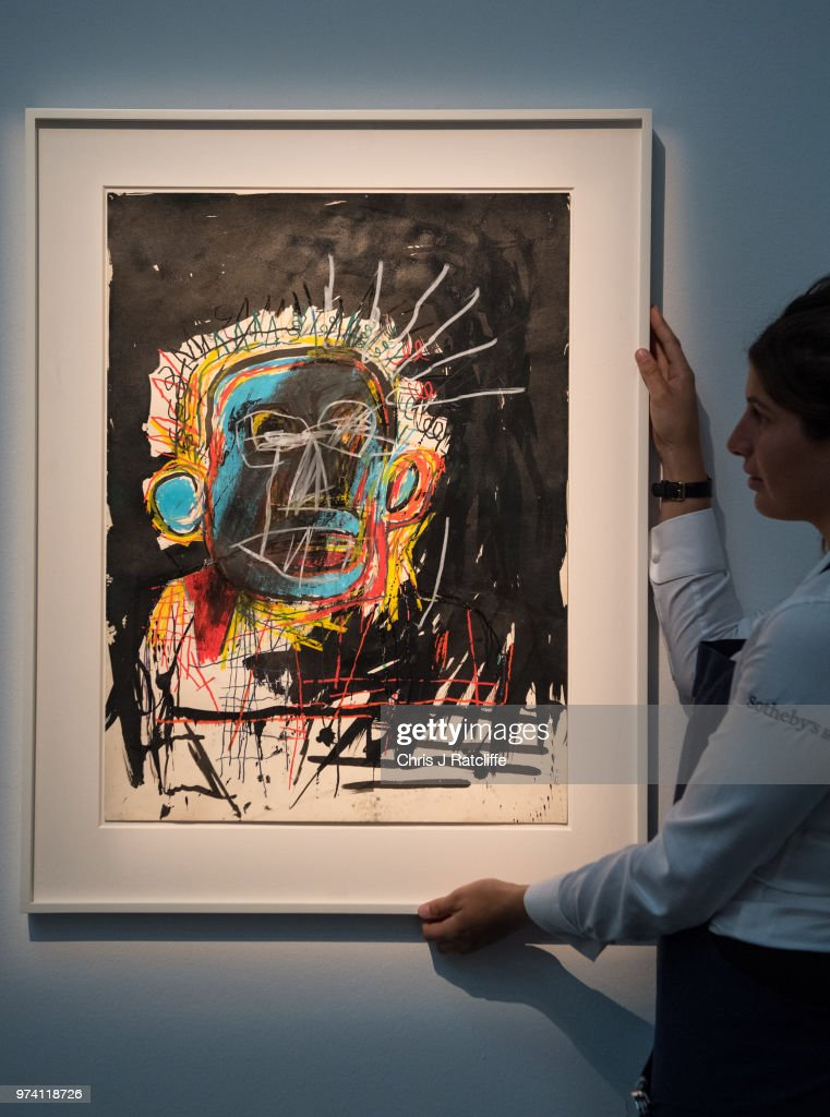 An art handler adjusts 'Untitled' by Jean-Michel Basquiat (estimated at £1.5 million to £2.5 million) during a preview of the Contemporary Art sale at Sotheby's on June 14, 2018 in London, England. The sale will take place on 26 June 2018 and includes works by artists Hockney, Freud and Basquiat.