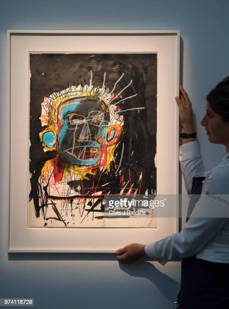 An art handler adjusts 'Untitled' by JeanMichel Basquiat during a preview of the Contemporary Art sale at Sotheby's on June 14 2018 in London England...