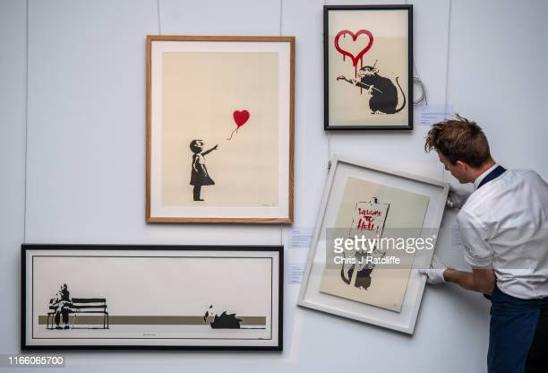 An art handler adjusts works by Banksy as he hangs them during a preview of the Banksy/Online sale at Sotheby's on September 5, 2019 in London,...