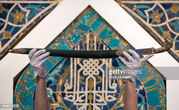 An art handler holds a fine Ottoman sword with lionhead hilt and scabbard during a press preview of Orientilist and Middle Eastern Art Week at...