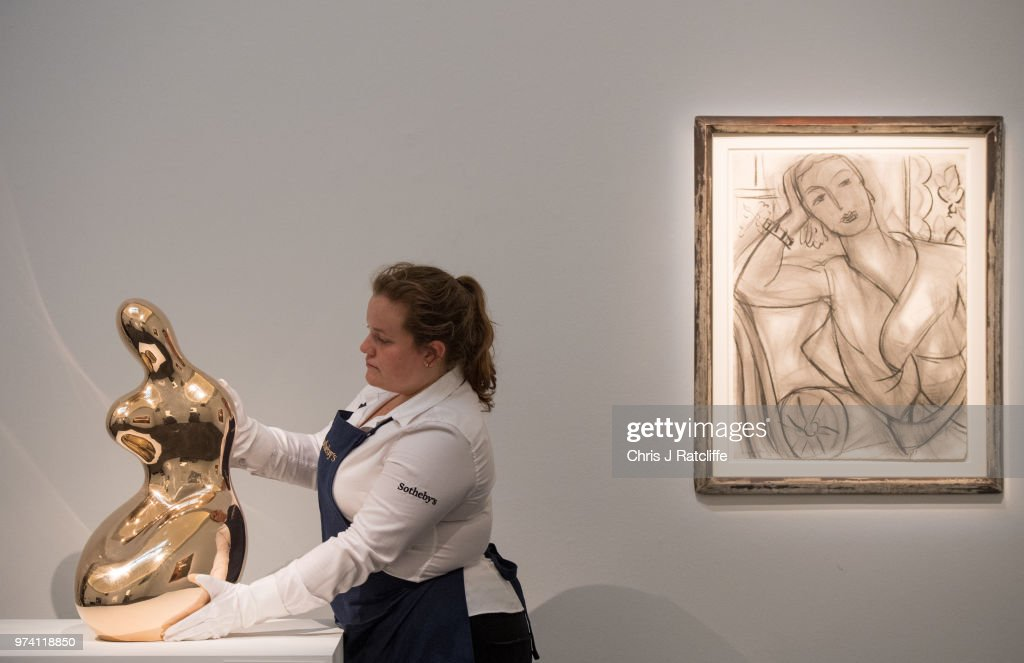 An art handler holds 'Demeter' by Jean Arp (estimated at £700,000 to £1 million) next to 'Portrait of Mrs Hutchinson' by Henri Matisse (estimated at £2 million to £3 million) during a preview of the Impressionist and Modern sale at Sotheby's on June 14, 2018 in London, England. The sale will take place on 19 June 2018 and includes works by artists Picasso, Monet, Kandinsky and Matisse.