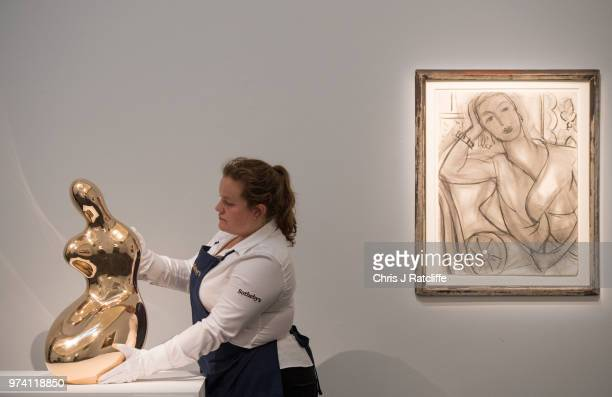 An art handler holds 'Demeter' by Jean Arp next to 'Portrait of Mrs Hutchinson' by Henri Matisse during a preview of the Impressionist and Modern...