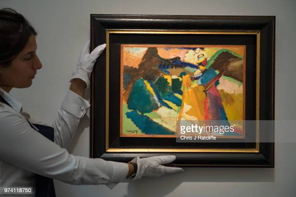 An art handlers 'Gabriele Munter im Freien vor der Staffelei' by Wassily Kandinsky during a preview of the Impressionist and Modern sale at Sotheby's...