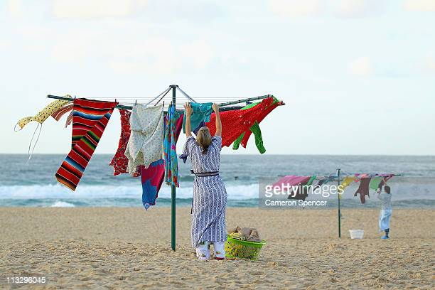 An art installtion consisting of eight Hills Hoists clothes lines complemented by eight 'mums hanging out washing' is seen at Bondi Beach on May 1...