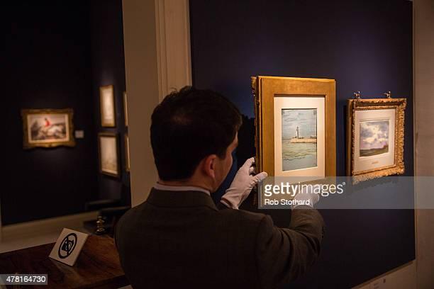 An art technician holds Claude Monet's 1968 piece 'Etude de ceil' at the Richard Green stand at Masterpiece Fair on June 23 2015 in London England...