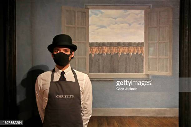 An art worker stands next to Rene Margritte's 'Le mois des vendanges' during preparations for the livestreamed art sales at Christie's Auction House...