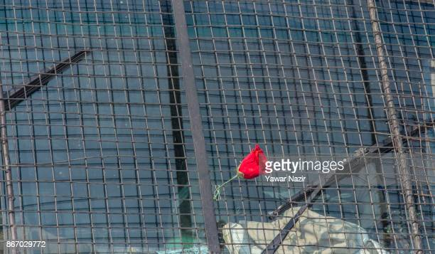 An artificial flower is attached the mesh of Indian police vehicle as their officer guards the deserted road during a strike on October 27 2017 in...