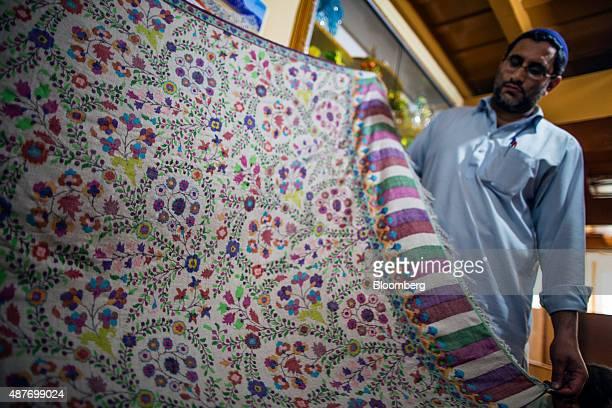An artisan displays a pashmina kani shawl at a home workshop in Srinigar Jammu and Kashmir India on Monday Aug 24 2015 Pashmina goats are no ordinary...