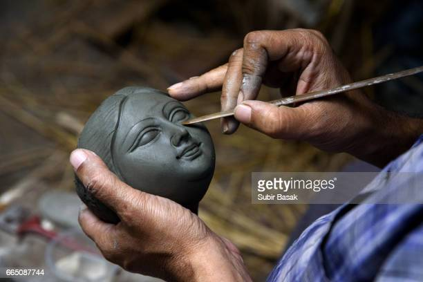 An artisan is making a clay-face of  Hindu Goddess Durga..