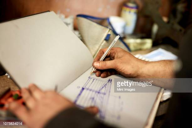 an artisan metal worker drawing up designs for a gate in a sketchbook - sketch stock pictures, royalty-free photos & images