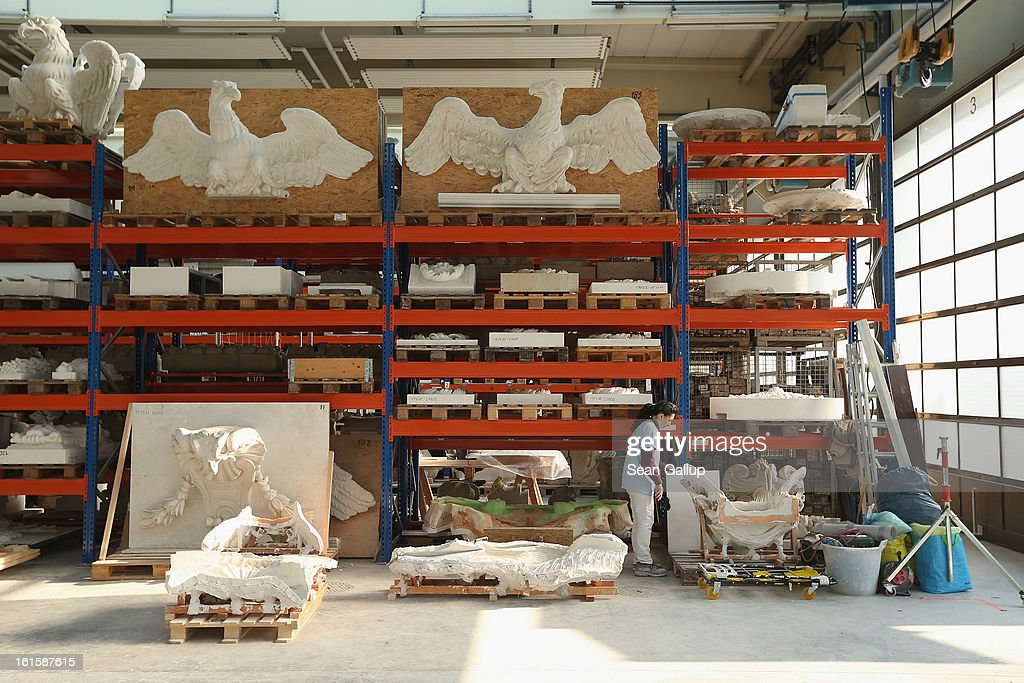 An artisan moves a silicon mould as plaster cast facade elements lie stored on shelves behind at the Schlossbauhuette studio where a team of sculptors is creating decorative elements for the facade of the Berliner Schloss city palace on February 12, 2013 in Berlin, Germany. The Berliner Schloss was the residence of the Prussian Kaiser and was among the major architectural landmarks of Berlin until it was heavily damaged by Allied bombing in 1945. The communist authorities of East Berlin demolished the building in the 1950s, and today's Berlin government is pursuing an ambitious project to rebuild the palace according to a design by Italian architect Franco Stella, which will recreate the facade of the building but with a modern interior at a cost of approximately EUR 590 million. The Humboldt Forum, the foundation leading the project, has given the Schlossbauhuette sculptors the formidable task of recreating the hundreds of architectural elements that decorated the facade, and though some original pieces were saved, more often the sculptors have only old black and white photos as reference.