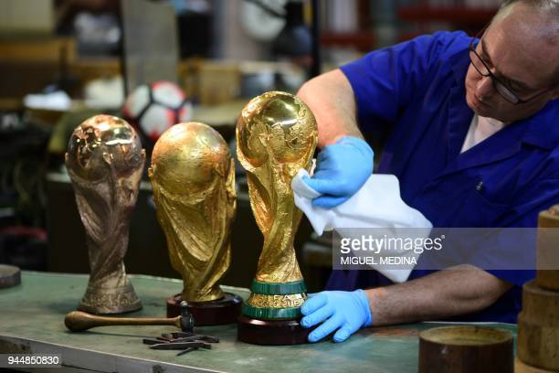 An artisan operator cleans with a cloth a replica of the FIFA football World Cup Trophy at the Italian trophy and medal manufacturer GDE Bertoni on...