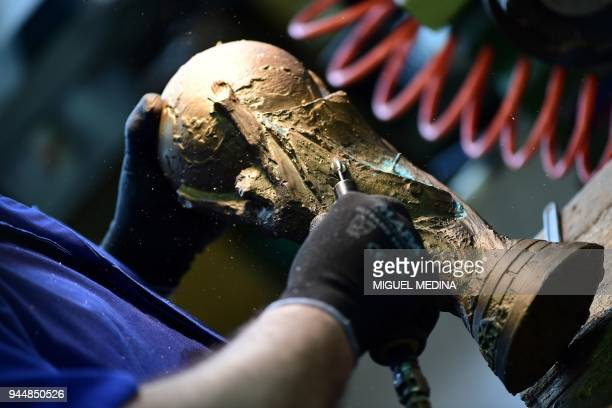 An artisan operator does the finishing on a raw trophy replica of the FIFA football World Cup Trophy at the Italian trophy and medal manufacturer GDE...