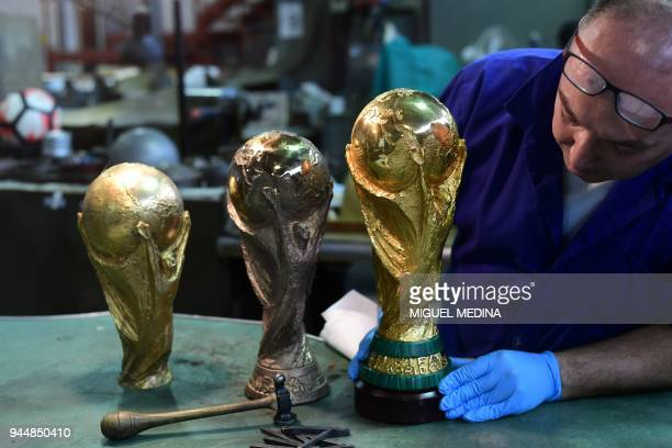 An artisan operator puts in a socle a replica of the FIFA football World Cup Trophy at the Italian trophy and medal manufacturer GDE Bertoni on April...