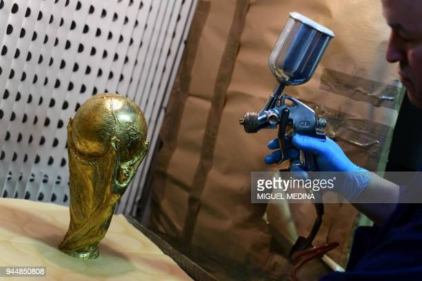 An artisan operator uses a spray painting to give a veil of protection on a replica of the FIFA football World Cup Trophy at the Italian trophy and...