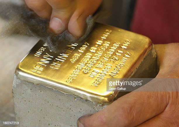 An artisan polishes a finished Stolperstein, which are concrete cobblestones afixed with a brass commemorative plaque, at the Stolpersteine...