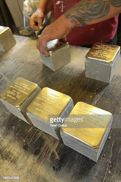 An artisan polishes finished Stolpersteine, which are concrete cobblestones afixed with a brass commemorative plaque, at the Stolpersteine...