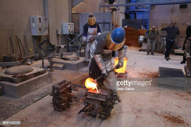 An artisan pours molten bronze into a cast to create a Berlinale bear trophy for the 68th Berlin International Film Festival at the Hermann Noack...