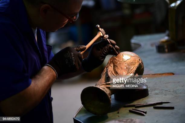 An artisan operator does the carving using a hammer and a chisel on a raw trophy replica of the FIFA football World Cup Trophy at the Italian trophy...