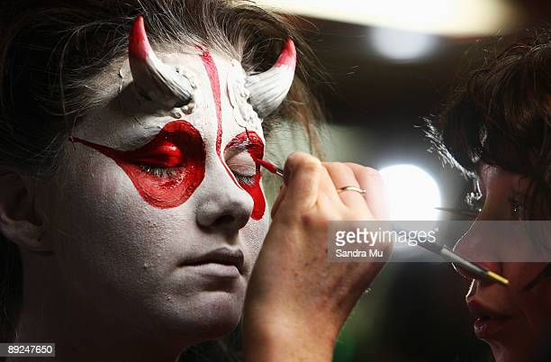 An artist applies paint to a model backstage during the New Zealand Body Art Awards at the Bruce Mason Centre on July 25 2009 in Auckland New Zealand