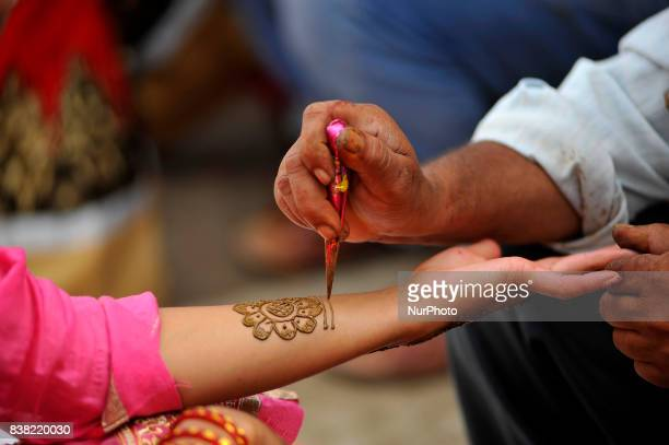 An artist applying Heena mehndi designs on a woman's hands during Teej festival celebrations at Pashupatinath Temple Kathmandu Nepal on Thursday...