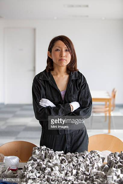 An artist at work in a studio, a woman in overalls with an artwork of